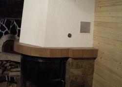1270 Това е камина с обло стъкло. С нея топлим триетажна къща в едно ботевградско село. Камерата е българска - на Деста с водна риза с мощност 25 kW. Монтирахме я на мястото на стара камина, която съборихме. За да запазим фурната до нея се наложи да направим нов комин. Облицовката направихме от обрязан гнайс, а плотовете - от керамика.