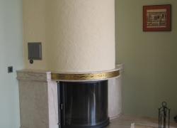 1535 Тази красива камина с обло стъкло и вертикално отваряне на вратата е с водна риза. Камерата е на българската фирма Деста. Облицовката, плотовете отстрани и настилката пред камината са от италиански мрамор Дайно. Апликациите са направени от жълта неръждавейка.